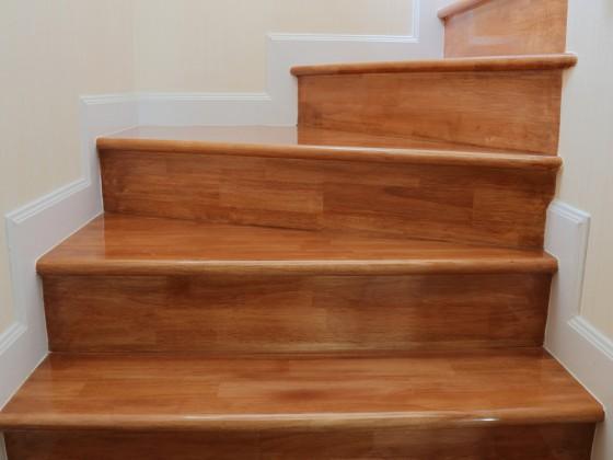 Rivestimento di gradini esistenti con alzatine e piani in legno massello lucidati.
